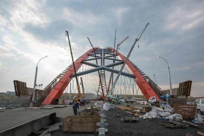 """Бугринским новый мост назвали далеко не сразу: в планах его чаще всего называли Оловозаводским — из-за одноимённого завода рядом с ним, а в сознании новосибирцев он всегда был просто «третьим» — у некоторых и до сих пор. Название <a href=""""https://news.ngs.ru/more/1414908/"""" target=""""_blank"""" class=""""_"""">выбирали с помощью голосования среди горожан</a> — новый мост предлагали назвать&nbsp;Горбатым, Леночкиным, Радужным и даже Городецким, а среди финалистов долгое время фигурировал Олимпийский мост — в честь Олимпиады в Сочи. В итоге остановились на Бугринском — по названию рощи, которую он пересекает"""