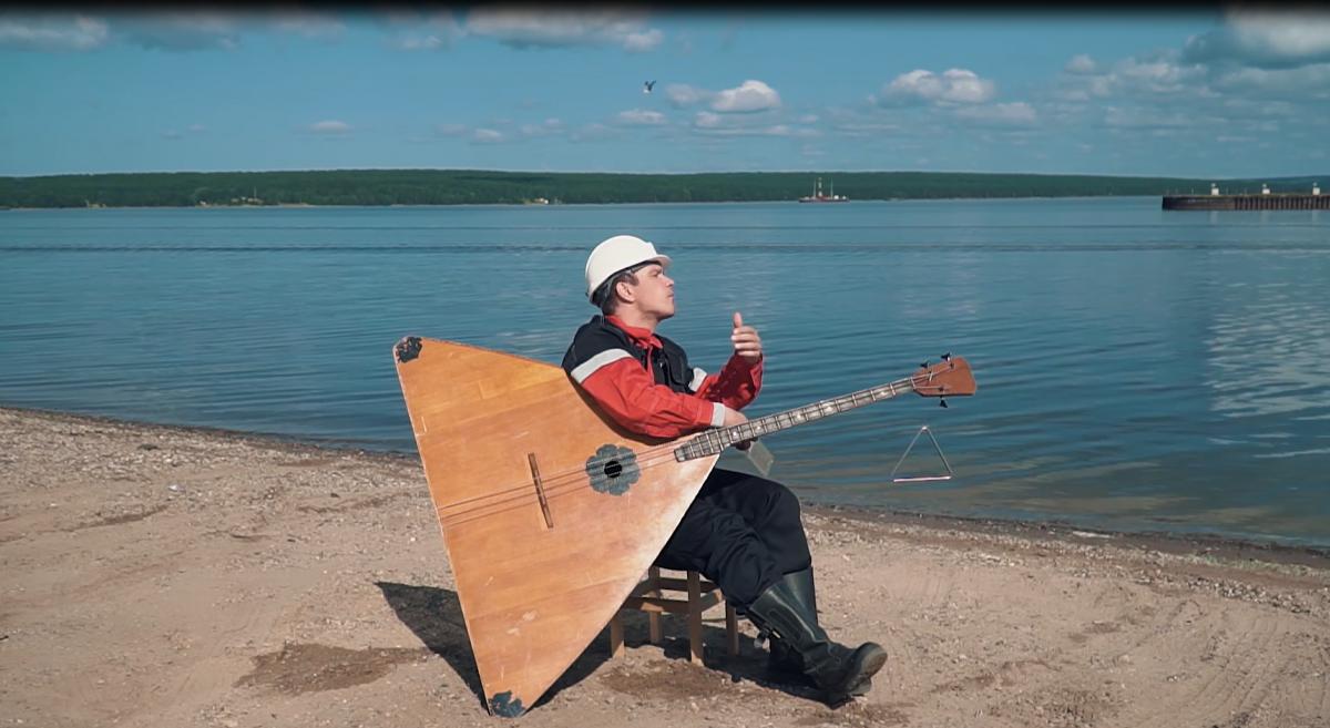 Музыкант играет возле объектов добычи нефти произведение Чайковского