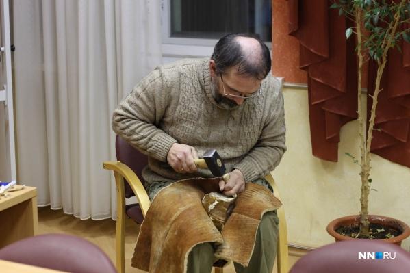 Илья Аникин с помощью ударной техники откалывает от нуклеуса пластину. В левой руке у него рог лося, а в правой — небольшая кувалда (вместо отбойника из камня)