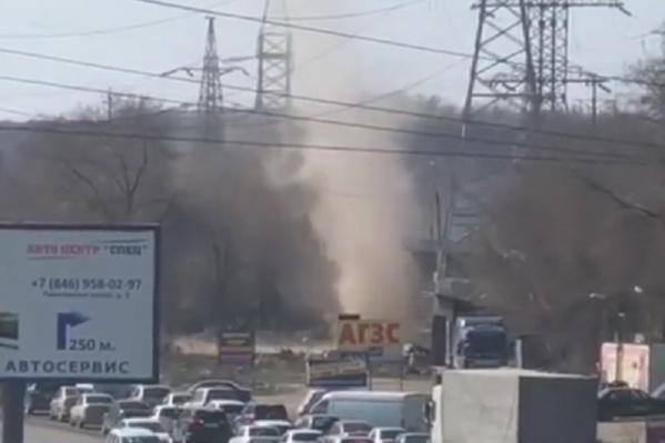 Огромный столб пыли метался по парковке