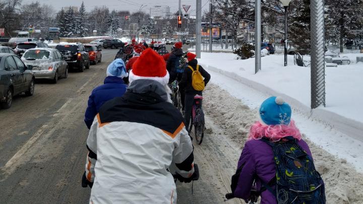 С белой бородой и ёлкой за спиной: полсотни Дедов Морозов устроили велопробег в центре Новосибирска