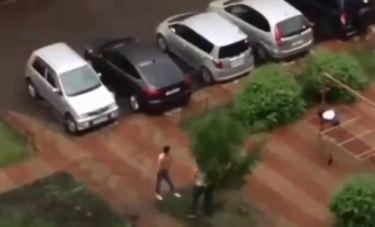 Двое парней во дворе бесцельно переломали ветви дерева