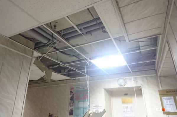 Некоторые потолочные плиты упали на пол, другие повисли на проводах