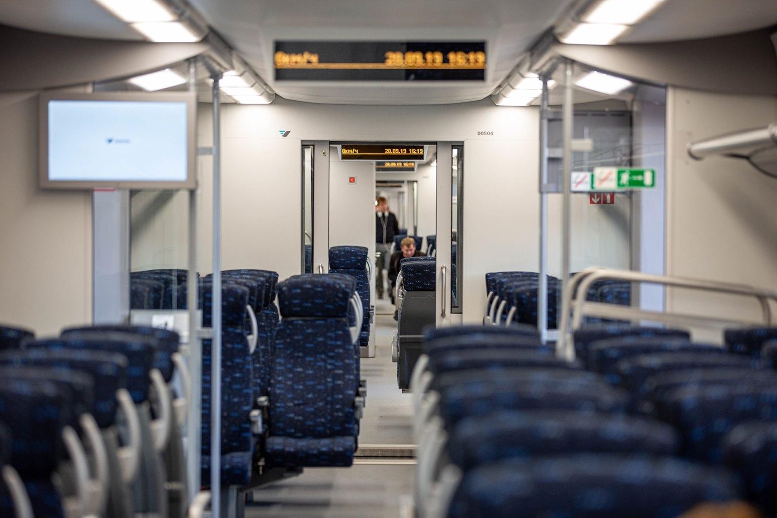 Поезд состоит из пяти вагонов, но между ними нет тамбура — только герметичные двери с огнестойким стеклом, которые плотно зафиксировали (они больше не хлопают, как в старых электричках). Сиденья в синей обивке расположены в два ряда: в одном по два кресла, в другом— по три