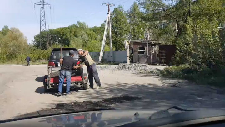 Двое мужчин на «Лексусе» заделали ямы на разбитой дороге