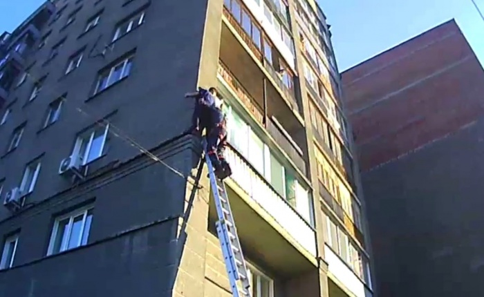 Спасатели помогают мужчине спуститься с карниза