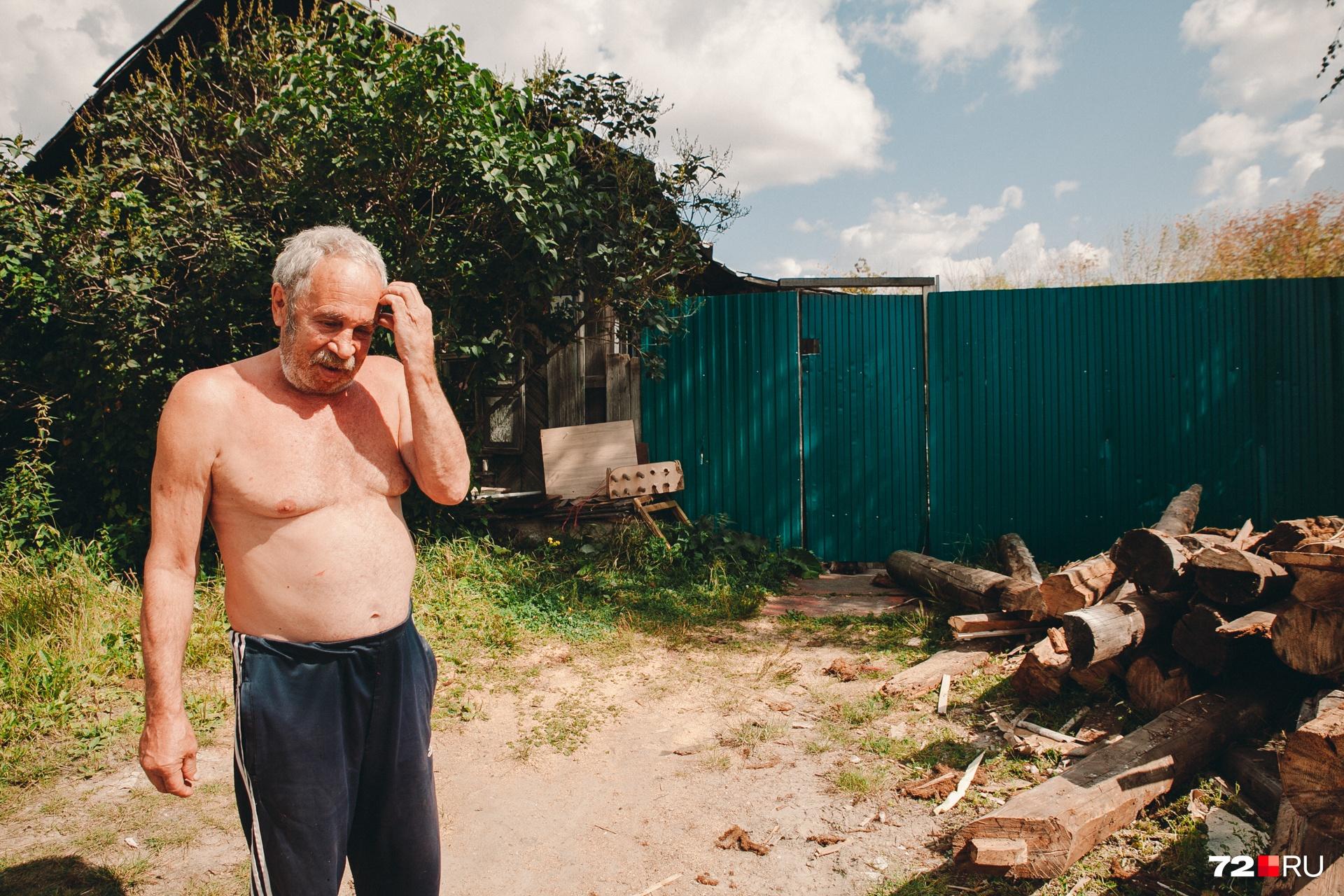 Тюменец показывает на бревна, которыми будет топить печь. Их ему отдали при сносе старого дома. История греет в буквальном смысле