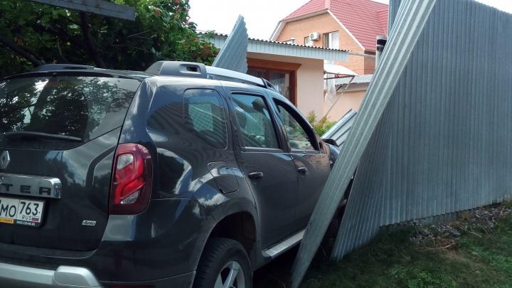 На Матросова «Рено» пробила забор после ДТП с «Приорой»