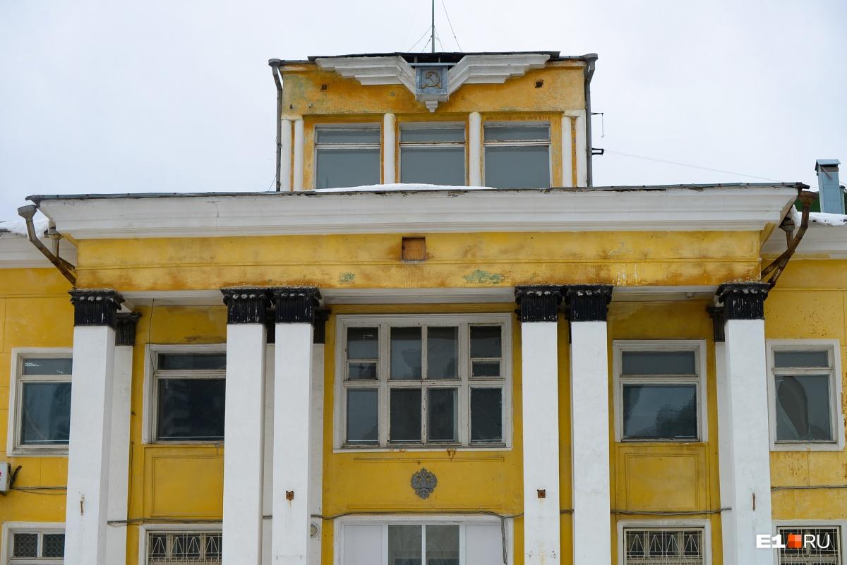 Башенка здания. Интересно, что сверху находятся серп и молот, а снизу — герб России