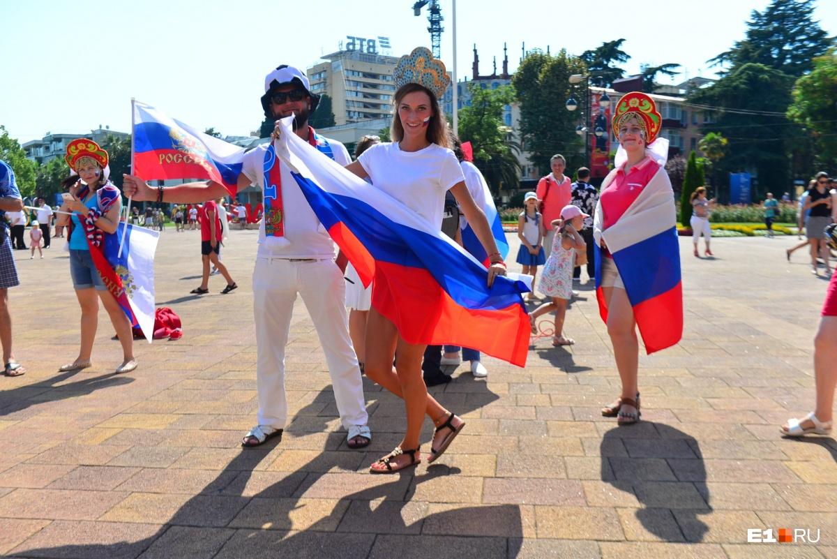 По городу гуляют люди в кокошниках и с флагами России