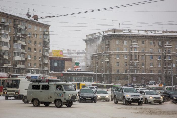 В городе стараются очистить не только дороги —рабочие сбрасывают снег с крыш