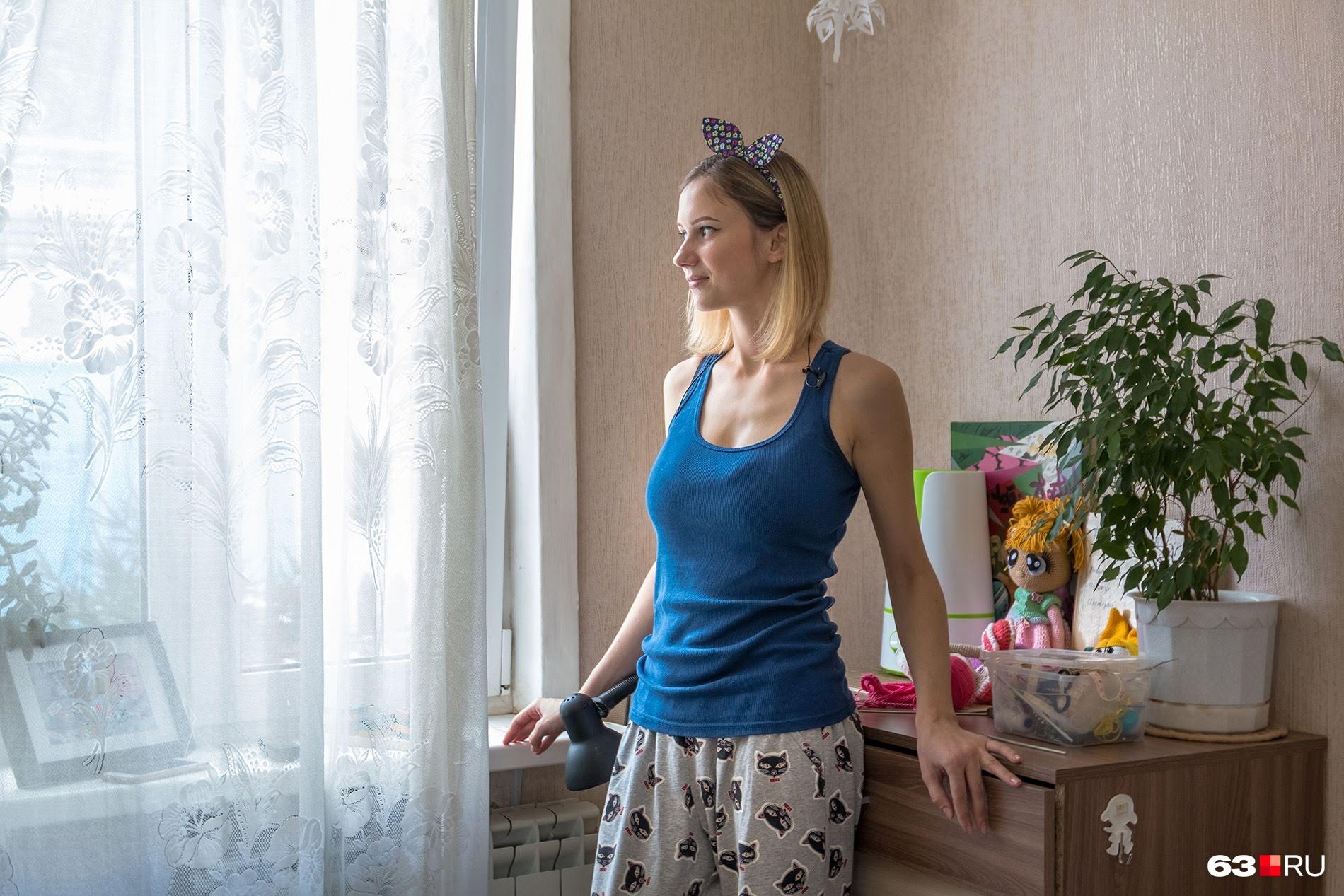Весь комод, что стоит позади Жени, забит пряжей, которую она выиграла в марафонах по вязанью