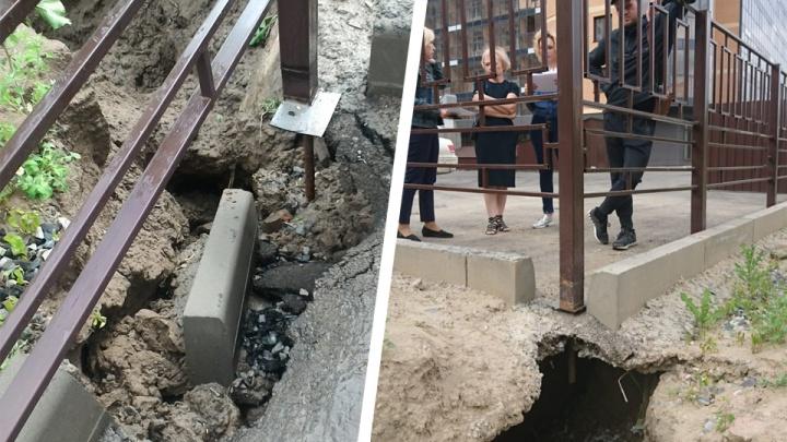 Столб повис: из-за дождей во дворе многоэтажки асфальт ушёл под землю
