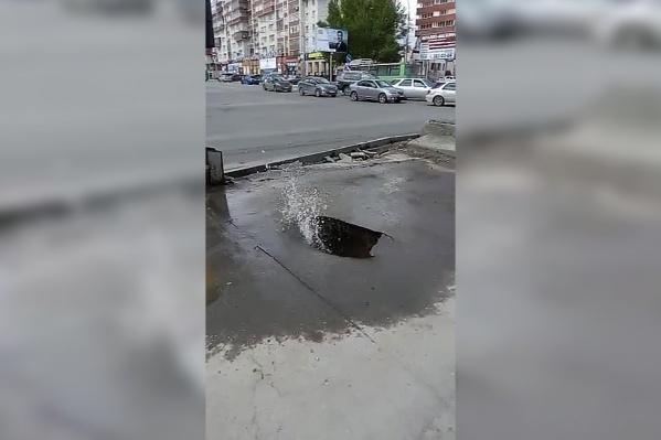 Вода начала хлестать из-под асфальта на тротуаре