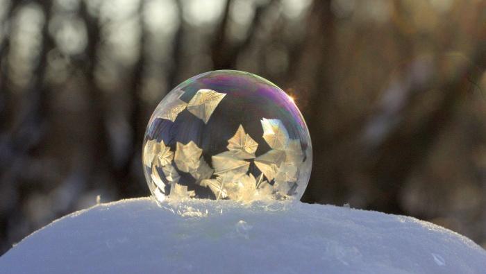 Кристаллы льда, похожие на листья, уже сковывают стенки мыльного пузыря
