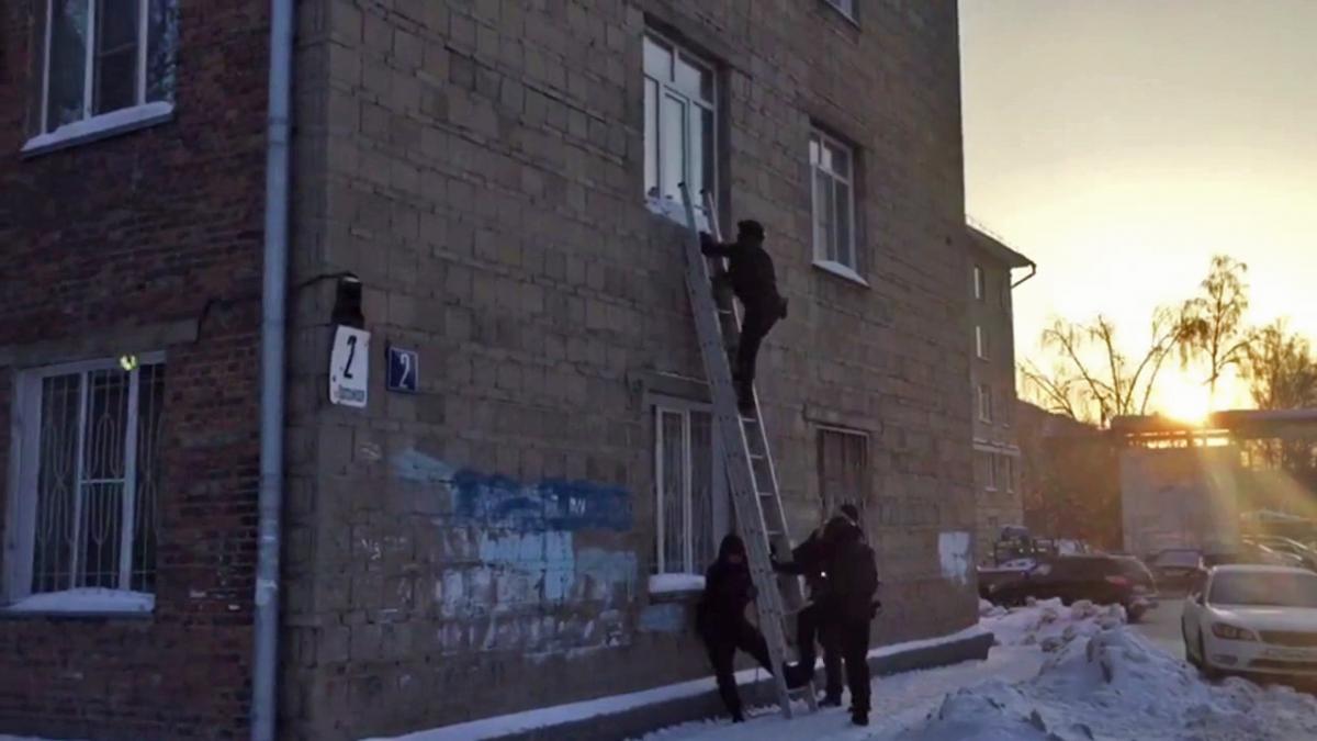 Чтобы проникнуть в квартиру с улицы, полицейские воспользовались лестницей и разбили окно