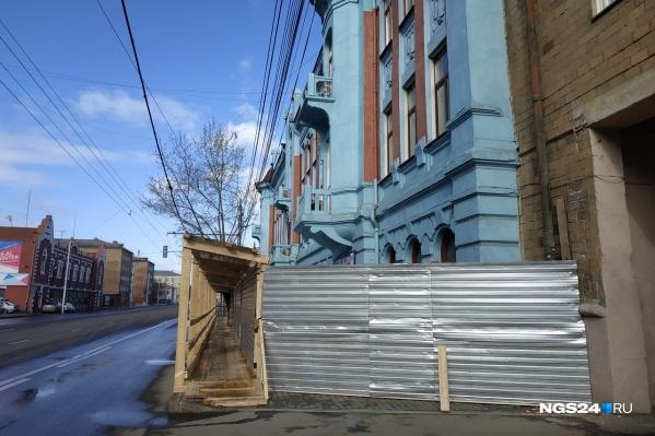 Теперь здание огорожено забором