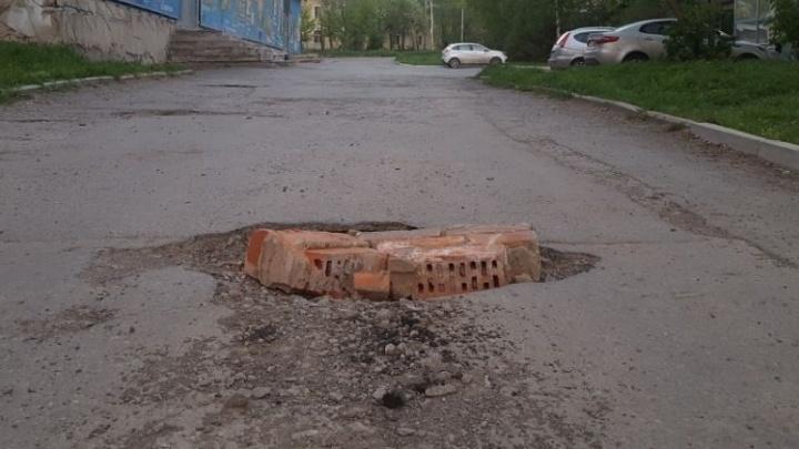 Дорожный ремонт по-уральски: на Эльмаше старую яму завалили кирпичами