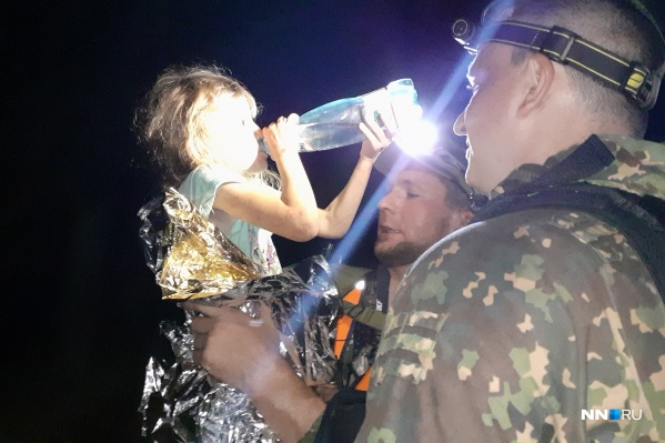 Потерявшейся девочке дают выпить чистой воды. Поисковики едва сдерживают улыбки счастья
