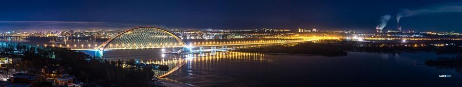 Недавно появившаяся достопримечательность города, Бугринский мост, виден из очень многих окон новосибирских высоток, но один из лучших видов на него — из новых домов на ул. Гэсстроевская. Из-за того, что левый берег чуть ниже правого, панораму, кроме подсвеченной арки моста, дополняют бесчисленные огни большого города.