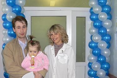 Первая пациентка детского отделения клиники «ВИЖУ!» пока предпочитает передвигаться на руках у папы, но приз за посещение уже держит сама