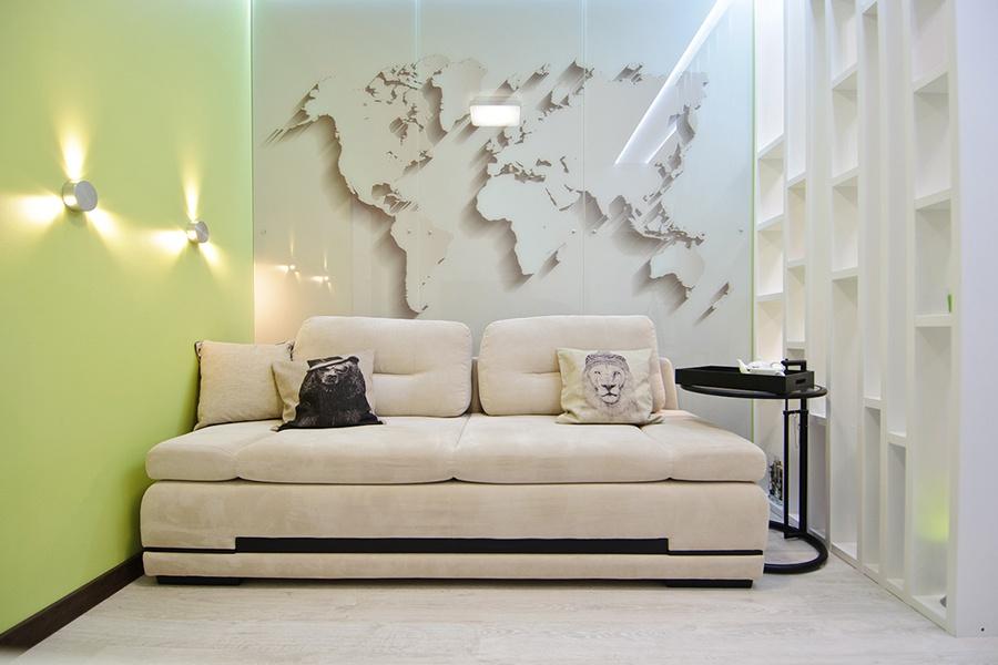 Заказчик просил разделить гостиную и спальню, поэтому за перегородкой появился отдельный раскладной диван, двуспальная кровать-трансформер осталась позади рабочего стола. Придиванный столик куплен в Cosmorelax. Карта над диваном напечатана на стекле — в дизайн-студии Mango пояснили, что из-за того, что стекло отражает свет, это расширяет пространство. Вместе со стеклом на кухне (для фартука) это обошлось в 56 тыс. руб.