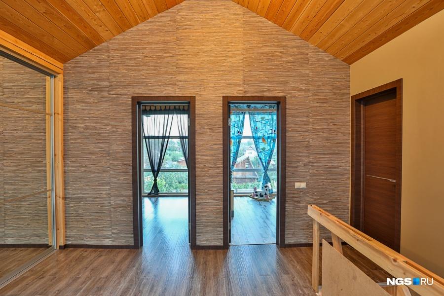 Так как входят в дом чаще через второй этаж, слева сделали гардеробную на 10 кв. м, справа — такую же по площади ванную комнату с окном, в которое видно деревья, но пока ее не доделали. Обои использовали натуральные, из бамбука.