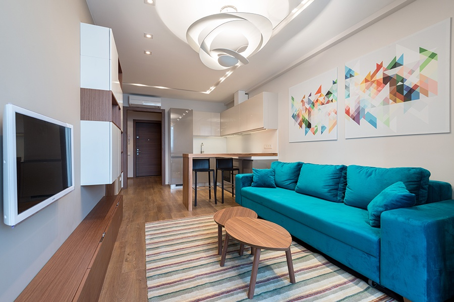 """«Семья очень творческая, и мы решили предложить им яркий эксперимент — акцентами являются желтая кровать, яркие картины, ковер и диван бирюзового цвета, — описывает Елена Каптерева. — Картины рисовали сами на компьютере и заказывали в интерьерной печати, диван — в компании """"Овация"""", столик из ИКЕА. Мы решили, что лампа в гостиной должна быть необычной, чтобы привлекать внимание, но быть при этом простой и лаконичной. Ее мы заказали в компании """"Артемида""""»."""