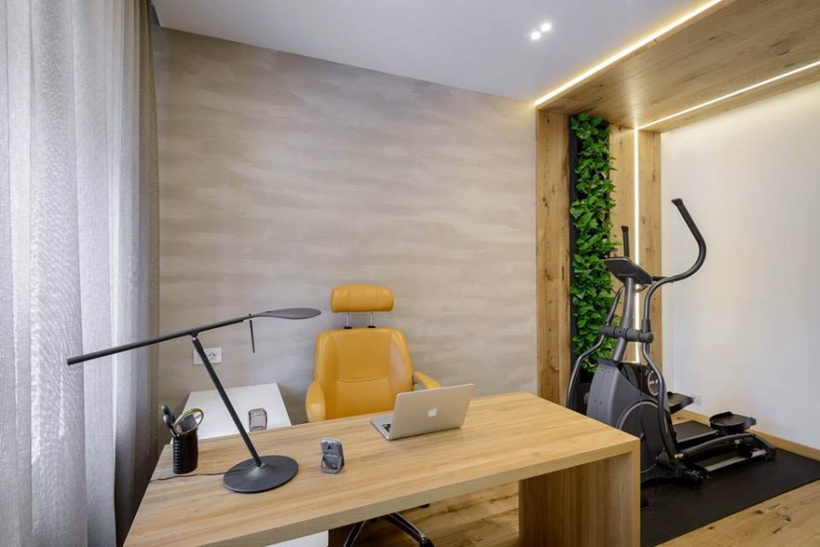 Недалеко от рабочего стола разместился эллиптический тренажер, возле него сделали «живую стену» — это вертикальная система озеленения с автополивом, и стоила она около 40 тыс. руб. (студия озеленения «ЛЕТО»). Часть потолка в кабинете тоже деревянная — это паркетная доска Barlinek Senses Intense на фанере. Подсветка сделана не только для декорирования, но и для растений.