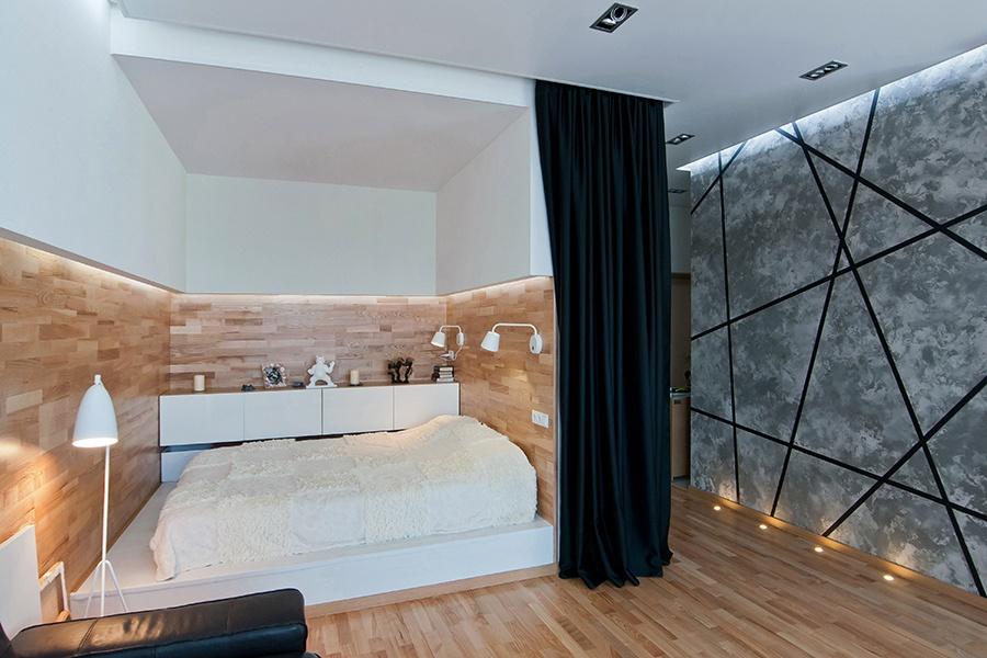 Спальная зона при желании отделяется плотной черной шторой. У стены рядом с кроватью поставили глубокие ящики для постельных принадлежностей, сделанные на заказ.
