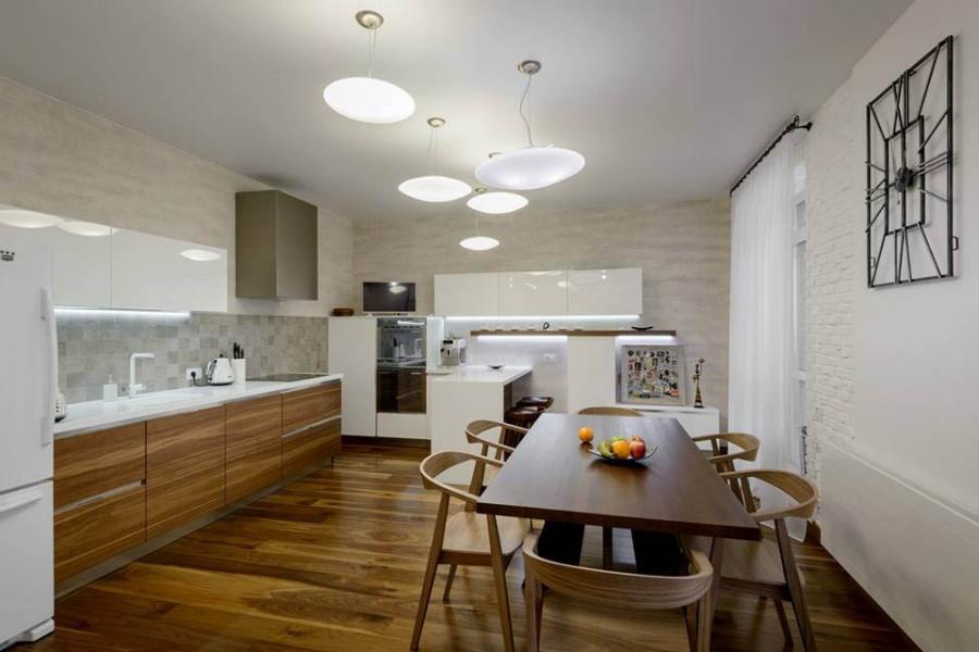 Кухню заказали в салоне Giulia Novars. Чтобы убрать с холодильника магниты, которые обычно добавляют в интерьер хаос, в IG-group заказали для них отдельную доску (справа, ближе к окну). Как добавила Ксения Елисеева, светильники «пустили облаками», не делая привязок к определенным зонам кухни-гостиной. Как и весь свет в квартире, их покупали в студии света «Аксиома». На полу — паркет Quick-Step цвета «орех, мистический сатин».