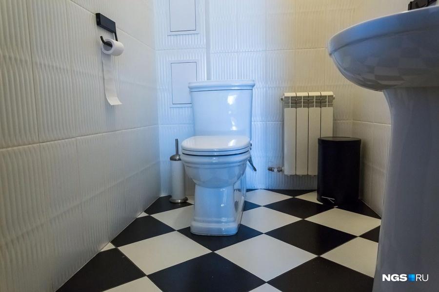 В лаконичном туалете с белыми стенами хорошо контрастирует шахматный пол.