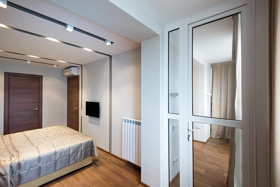 В квартире сделали перепланировку, присоединив лоджию около 8 кв. м, поэтому воздуха стало больше. Площадь коридора минимизировали, сделав вход в спальню через прозрачную дверь гостиной, и поэтому появилось место для отдельной гардеробной, в которую есть выход из спальни. Рельефный потолок со светильниками задуман, чтобы сделать комнату более квадратной.