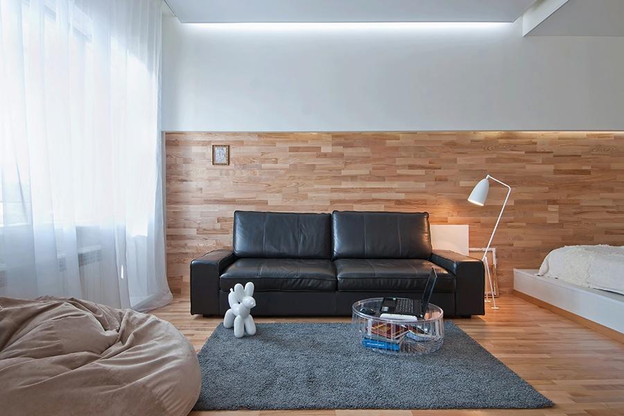 Чтобы квартира казалась более просторной, использовали светлые тона и разноплановое освещение. На полу и стенах гостиной — трехполосная паркетная доска. Диван — «Кивик» от IKEA, бескаркасное кресло — Ambient Lounge. Для хранения вещей установлены шкафы-купе в прихожей.