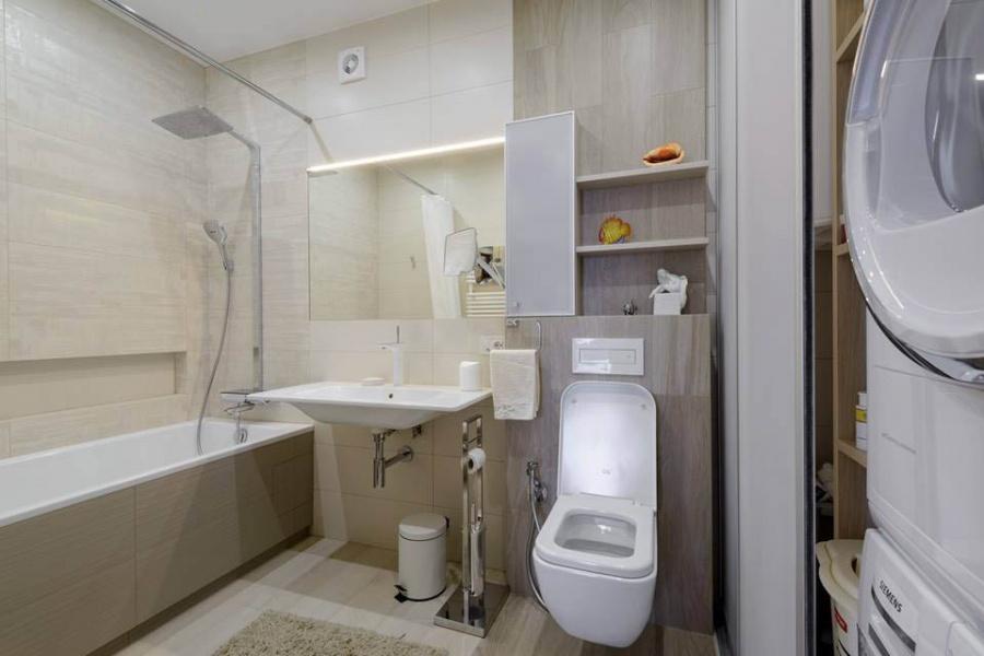 В одном из санузлов разместили ванную. На стенах — керамогранит Mirage Signature с лаконичным декором. Возле ванной предусмотрели нишу для косметики, для этих же целей возле зеркала сделали небольшой шкаф.